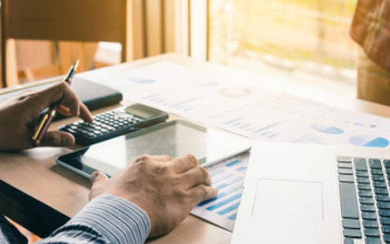 Mann sitzt am Schreibtisch und bewertet eine Immobilie